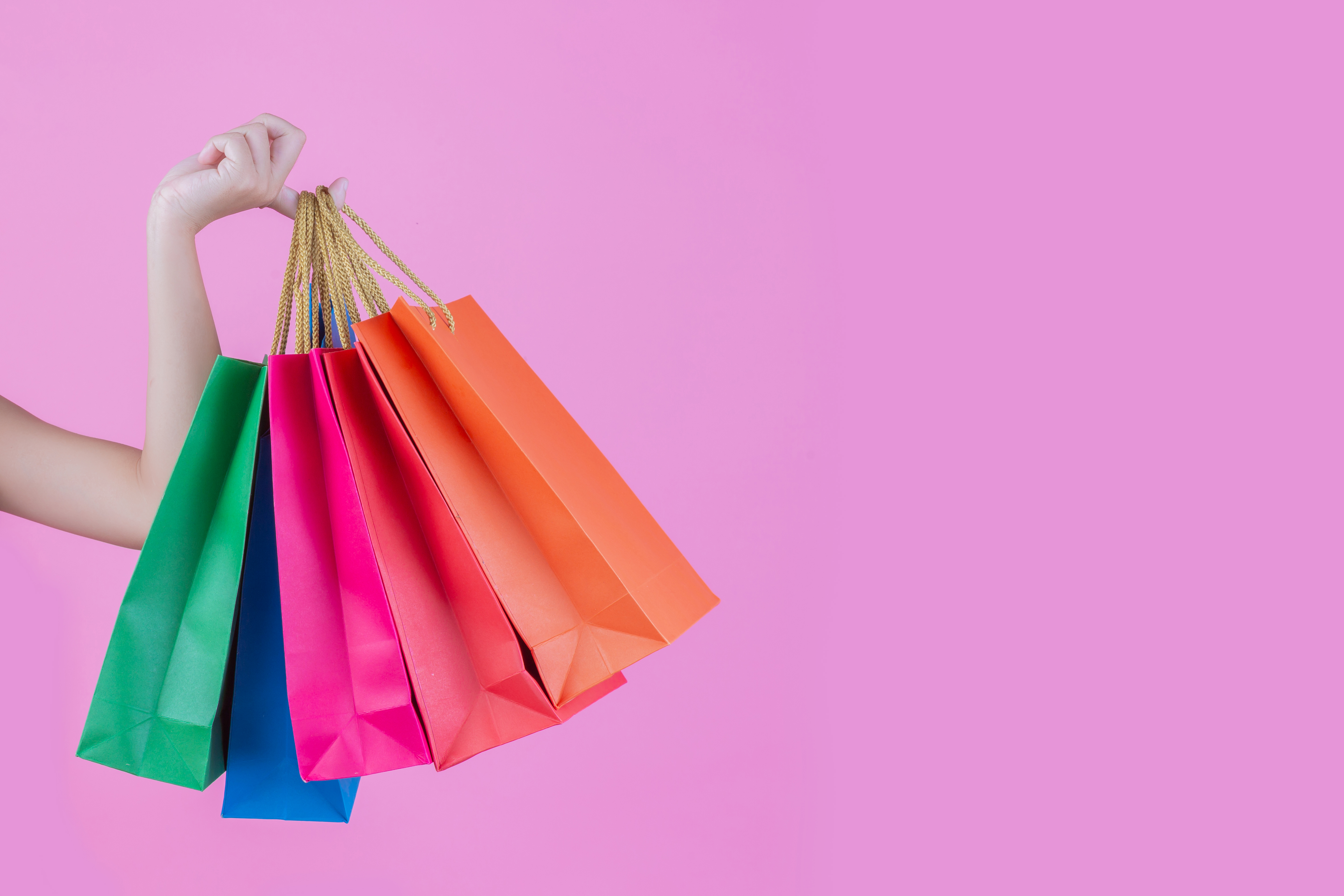 The girl holds a fashion shopping bag and beauty on a pink background.